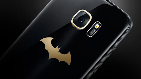 Closeup of the rear camera of Galaxy S7 edge Injustice Edition which is lined in gold and there is a gold Batman logo beneath